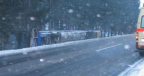 Schulbus kippt über Böschung, Lenker übersieht Zug (Bild: FF Wallern)