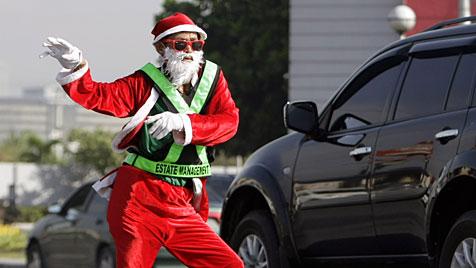Weihnachtsmann dirigiert tanzend Verkehr in Manila (Bild: EPA)