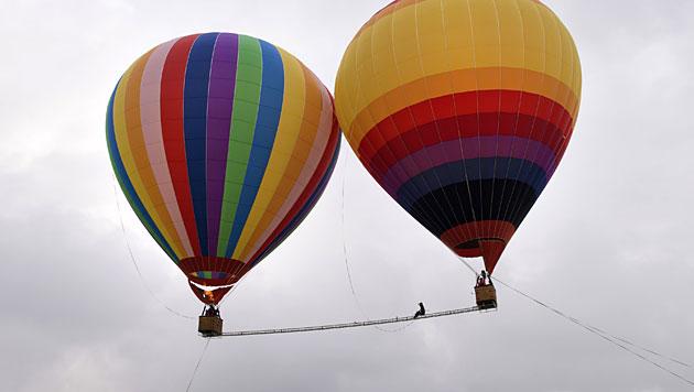 Artist macht Seiltanz zwischen zwei Ballons (Bild: AFP)