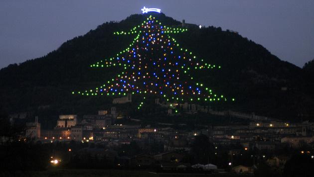 Weltgrößter Weihnachtsbaum in Italien illuminiert (Bild: AP)