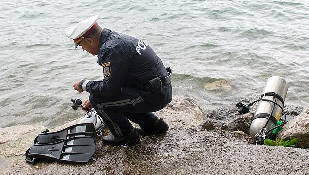 Ein Polizist begutachtet die Tauchausrüstung des Polen. (Bild: APA/WERNER KERSCHBAUMMAYR)