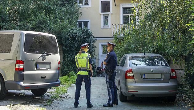 Zwei Polizeibeamte vor dem Haus in Graz, in dem die Tat stattgefunden hatte (Bild: APA/ERWIN SCHERIAU)
