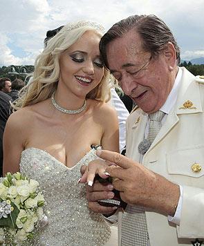 """Richard Lugner steckt """"Spatzi"""" den Verlobungsring an den Finger. (Bild: APA/GERT EGGENBERGER)"""