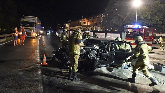 Feuerwehrleute reinigen nach dem verheerenden Zusammenstoß die Fahrbahn. (Bild: APA/dpa)