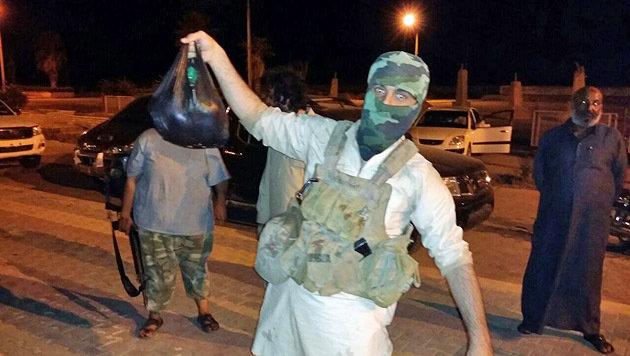 Firas posiert stolz mit einem Plastiksack, in dem sich ein Kopf befindet. (Bild: Privat)