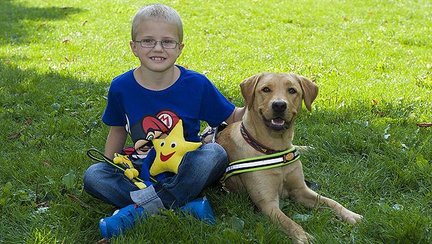 """Der siebenjährige Julian mit Diabetikerwarnhündin """"Bella"""" (Bild: Mars Austria)"""