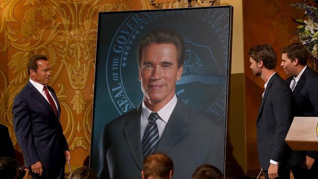 Arnold Schwarzenegger betrachtet mit den Söhnen Patrick und Christopher sein Porträt. (Bild: AFP)