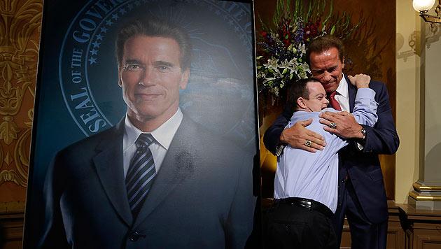 Schwarzenegger wird von seinem Ex-Mitarbeiter John Masterson, 28, der das Down Syndrom hat, umarmt. (Bild: AP)