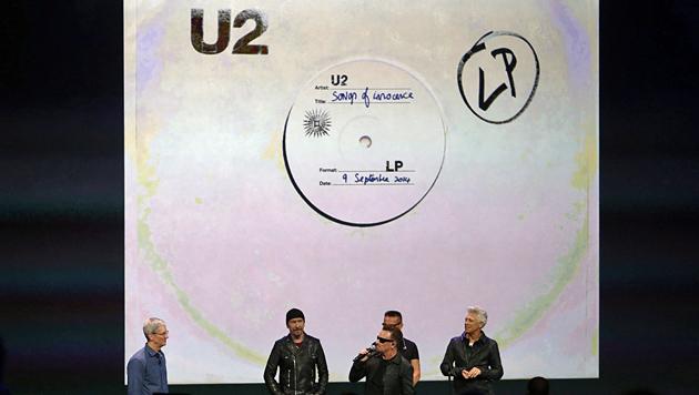 """U2 mit Apple-Chef Tim Cook vor dem Cover ihres neuen Albums """"Songs of Innocence"""". (Bild: APA/EPA/Monica Davey)"""