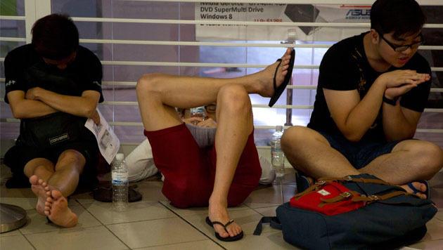 Vor einem Apple Store in Singapur kampierten die Apple-Jünger kurzerhand am Boden. (Bild: AP)