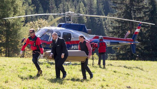 Einer der toten Alpinisten wurde von Polizisten und einem Bestattungsmitarbeiter abtransportiert. (Bild: APA/JOHANN GRODER)