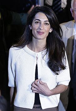Amal Clooney reiste sehr stylisch nach Athen: Sie trug eine weiße Cardigan-Jacke zu Khakihosen. (Bild: AP)