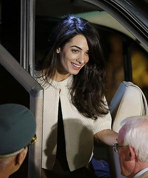 Amal Clooney lächelt im Blitzlichtgewitter.