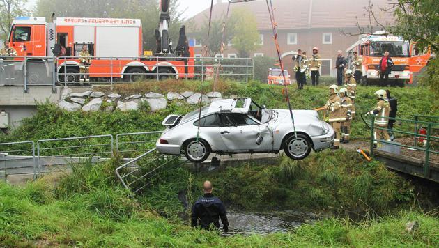 Die Feuerwehr hievte den Sportwagen nach dem Rettungseinsatz aus dem Bach. (Bild: APA/BERUFSFEUERWEHR LINZ)