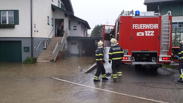 Helfer der Feuerwehr pumpten in Bad Ischl zahlreiche Garagen und Keller aus. (Bild: APA/BARBARA GINDL)