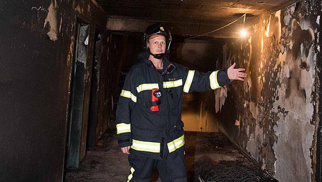 Thomas Schurz, Einsatzleiter der FF Steyr, zeigt das Ausmaß des Schadens im Flur des Wohnhauses. (Bild: Werner Kerschbaummayr, foto-kerschi.at)