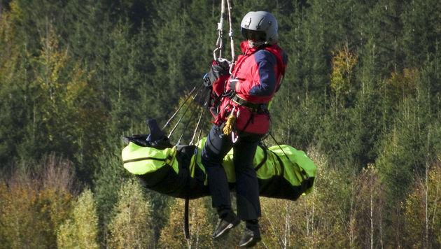 Die Bergung eines der beiden Opfer durch einen Bergretter (Bild: APA/DANIEL SCHARINGER)
