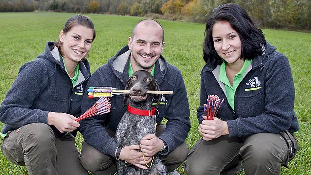 """Für das Foto nimmt Hund """"Igor"""" die Raketen ins Maul. Die Trainer Isabella, Florian und Andrea. (Bild: Markus Tschepp)"""