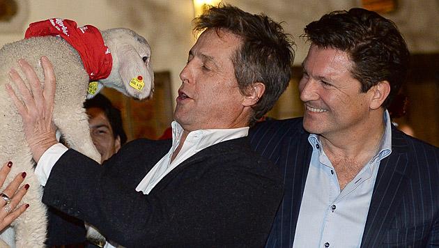 "Hugh Grant herzt Schaf ""Mango"", Francis Fulton-Smith schaut zu. (Bild: APA/BARBARA GINDL)"