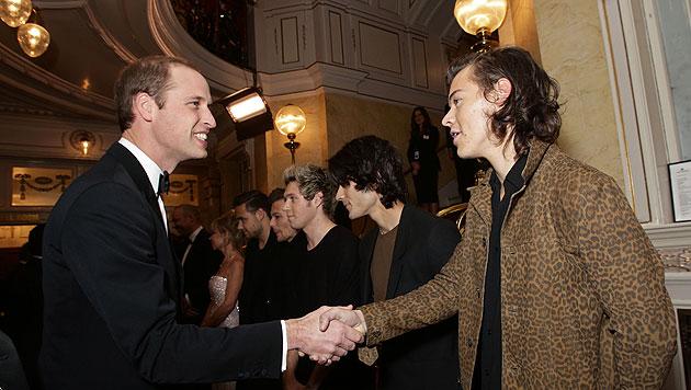 Prinz William schüttelt die Hand von Harry Styles. (Bild: AP)