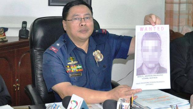 Stolz präsentiert ein Beamter das Foto des mutmaßlichen Betrügers. (Bild: Polizei)