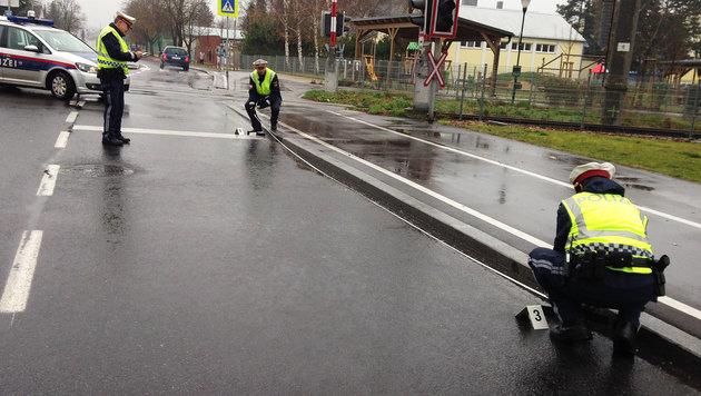 Polizisten vermessen die Unfallstelle in Fischamend, wo ihr Kollege angefahren wurde. (Bild: ORF/GERNOT ROHRHOFER)