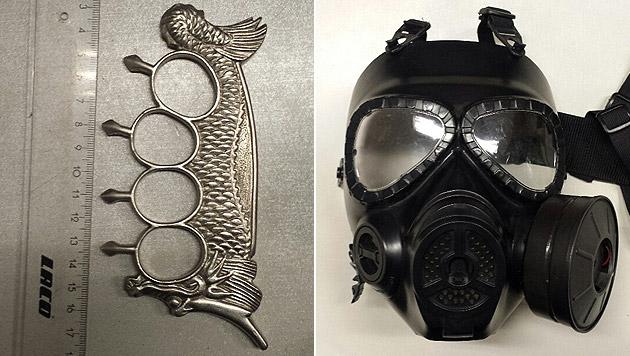 Ein sichergestellter Schlagring sowie eine Gasmaske (Bild: Polizei)