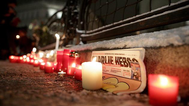 """Kerzen und eine """"Charlie                Hebdo""""-Ausgabe vor der französischen Botschaft in                Wien (Bild: APA/GEORG HOCHMUTH)"""