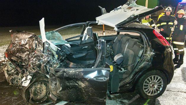 Einsatzkräfte neben einem der Unfallfahrzeuge (Bild: APA/WERNER KERSCHBAUMMAYR)