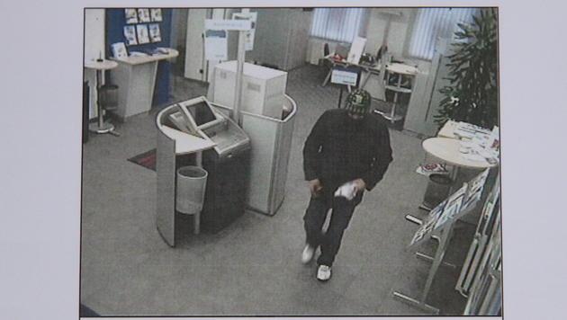 Kurz nach 8.30 Uhr stürmte der maskierte Mann die Bankfiliale. Der Täter stammt aus Armenien. (Bild: Christoph Gantner)