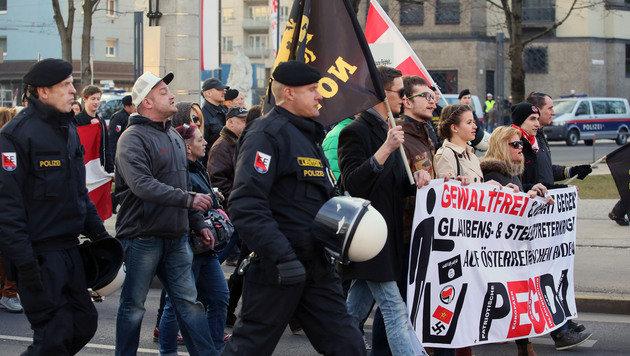 """Die Teilnehmer der Pegida-Kundgebung in Linz beim """"Spaziergang"""" zum Volksgarten und zurück (Bild: APA/RUBRA)"""