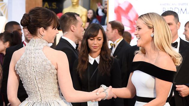 Felicity Jones und Reese Witherspoon begrüßen sich am roten Teppich. (Bild: AFP)