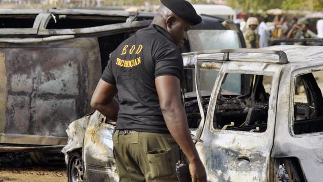 Ein Ermittler in Nigeria inspiziert den Tatort nach einem Selbstmordanschlag auf eine Busstation. (Bild: AP)
