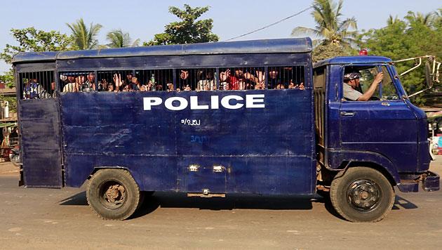 Verhaftete Studenten werden in einem Polizeiauto abtransportiert. (Bild: APA/EPA/Nyein Chan Naing)