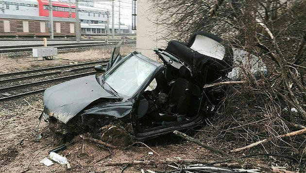 Das schwarze Cabrio wurde bei dem 15-Meter-Absturz völlig zerstört. (Bild: APA/BERUFSRETTUNG WIEN/UNBEKANNT)