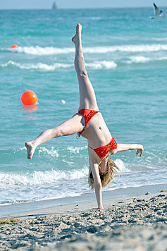 Schauspielerin Candice Accola beim Radschlagen am Strand. (Bild: Viennareport)
