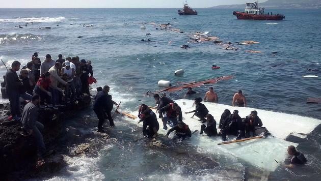 Flüchtlinge werden vom Wrack eines Bootes gerettet, das vor der Insel Rhodos gekentert war. (Bild: EPA/LOUKAS MASTIS)
