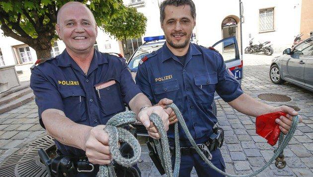 Die beiden Polizisten präsentieren jenes Abschleppseil, das half, ein Leben zu retten. (Bild: MARKUS TSCHEPP)
