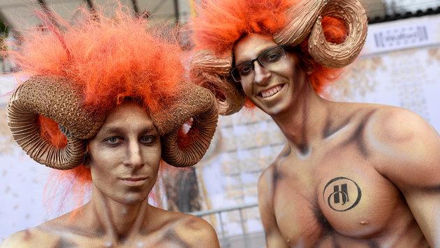 Zwei Herren mit nackte Oberkörpern und Hörnern (Bild: APA/ROLAND SCHLAGER)