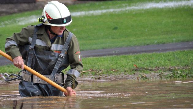 Ein Feuerwehrmann inmitten eines überfluteten Geländes in Feldbach (Bild: APA/LFV/MEIER)