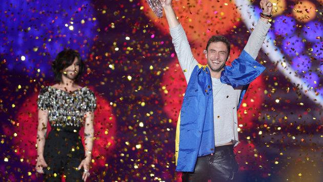 Mans Zelmerlow mit dem Siegerpokal - Vorjahressiegerin Conchita Wurst lächelt im Hintergrund. (Bild: APA/GEORG HOCHMUTH)