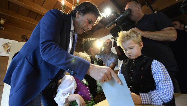 Die Enkerl Luisa, Benjamin und Jakob helfen Landeshauptmann Franz Voves (SPÖ) bei der Stimmabgabe. (Bild: APA/HANS KLAUS TECHT)