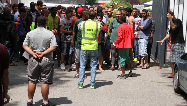 Mehr als hundert Asylwerber drängen sich beim Tor zum Linzer Polizeisportverein. (Bild: Christoph Gantner)