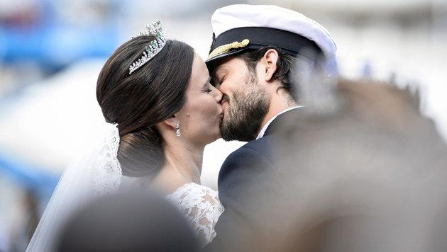 Sofia und Carl Philip küssen sich lachend in der Kutsche. (Bild: APA/EPA/Pontus Lundahl /TT)