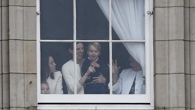 Mit seiner Nanny schaut der Mini-Prinz aus einem Fenster des Buckingham-Palastes. (Bild: EPA)