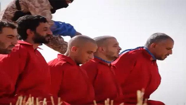 Ein IS-Kämpfer befestigt eine Zündschnur an den Hälsen der Männer. (Bild: YouTube.com)