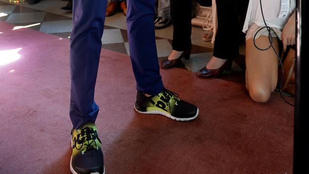 """Petzner, auch bekannt für Auftritte mit """"Flügelschuhen"""", kam in schwarz-neongrünen Sneakers. (Bild: APA/ROLAND SCHLAGER)"""