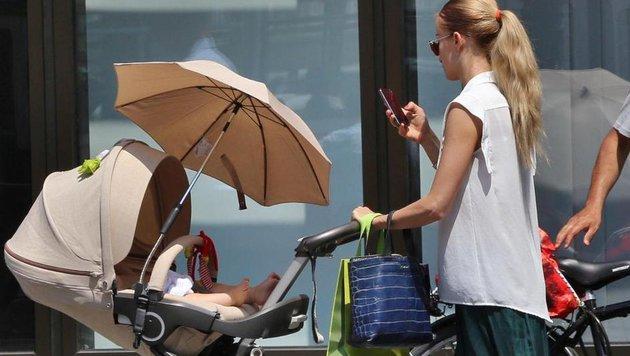 Sarkissova mit Lev im Kinderwagerl, den Blick aufs Handy gerichtet. (Bild: Starpix/A. Tuma/SPY)