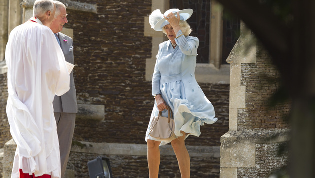 Herzogin Camilla muss ihre Kleidung gegen den Wind verteidigen - Ehemann Charles gefällt das. (Bild: AP)