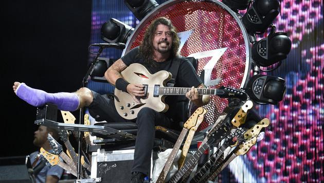 Dass ein Sturz von der Bühne auch böse enden kann, beweist Dave Grohl. Er muss mit Gipsfuß spielen. (Bild: Nick Wass/Invision/AP)